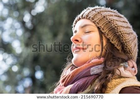 Young woman enjoying sunlight at the park. - stock photo