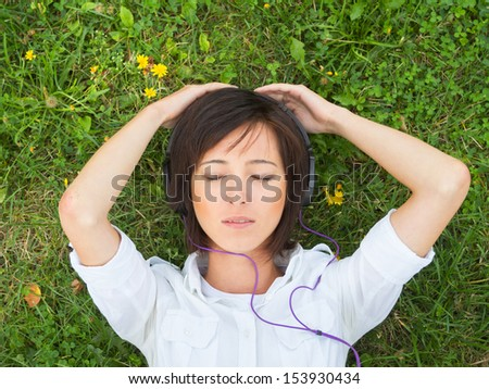 Young woman enjoying the music with closed eyes on a summer meadow - stock photo
