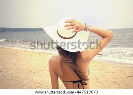 Young woman enjoying the ocean view in a summer vacation.Summer vacation and healthy lifestyle concept.Lens flares