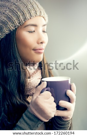 Young woman enjoying the scent of coffee she is holding in her hands. - stock photo