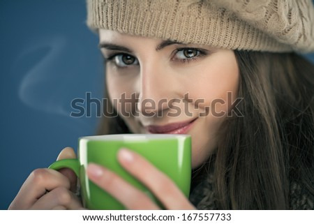 Young woman enjoying the scent of tea she is holding in her hands.