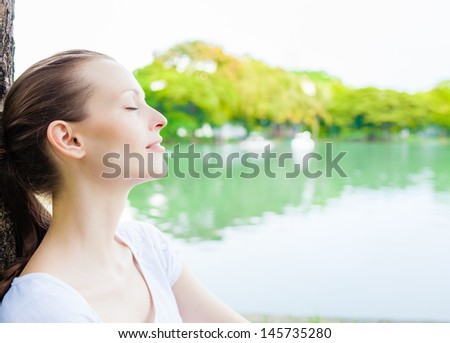 Young woman enjoying the sun in the park - stock photo