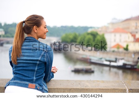 young woman enjoying the view from a bridge - stock photo