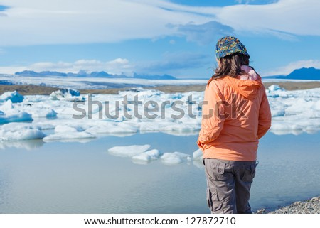 Young woman enjoying the view Jokulsarlon a lake in Iceland where icebergs collapsing from Vatnajokull glacier are floating around. - stock photo