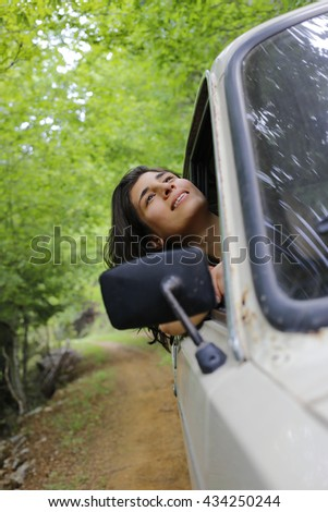 Young woman enjoying to the travel in the nice forest with her boyfriends classic car.