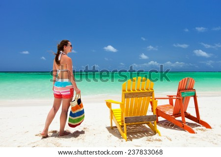Young woman enjoying vacation at tropical beach with two colorful wooden chairs on white sand and turquoise ocean water - stock photo