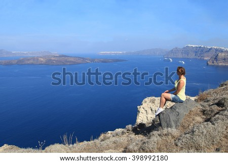 Young woman enjoying view of a volcano from the top of Santorini island, Greece - stock photo