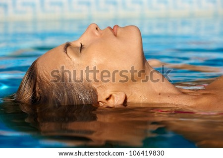 Young woman enjoying water and sun in outdoor swimming pool. - stock photo