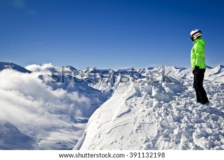 young woman enjoying winter on top of the mountain