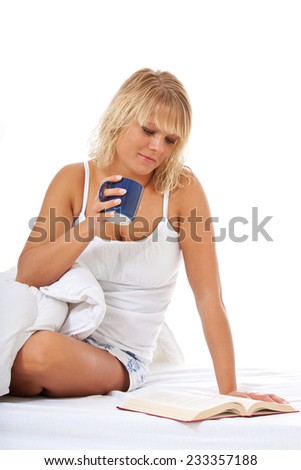 Young woman enjoys cup of coffee in bed. All on white background. - stock photo