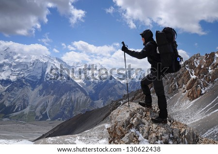 Young woman enjoys spectacular view to high mountains, Kyrgyzstan, Central Asia - stock photo