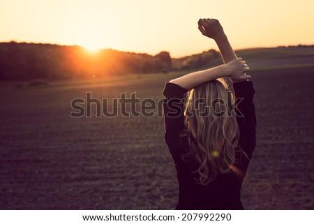 Young woman enjoys sun beams - stock photo