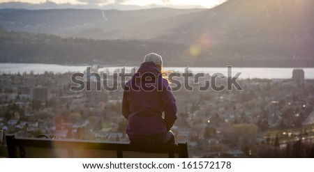 Young Woman Enjoys the View from Park Bench - stock photo