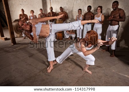 Young woman evades a kick during a Capoeira demonstration - stock photo