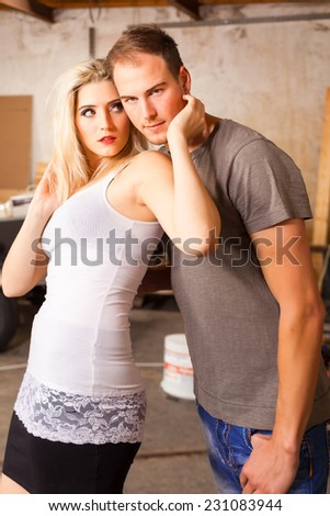 Young woman exchanged caresses with a man, both standing sideways and you hugged him. / Young woman exchanges of affection with a man. - stock photo