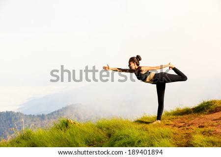 Young woman exercises yoga in the mountains - stock photo