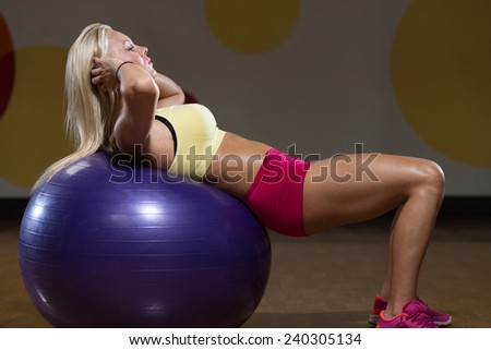 Young Woman Exercising Abdominals In Fitness Club