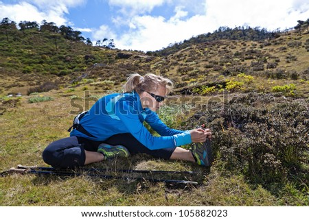Young woman exercising and stretching in mountains, nordic walking in summer