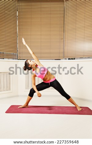 Young woman exercising arm and leg in straight line yoga pose looking at palm