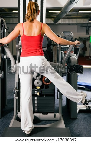 Young woman exercising at a machine that strengthens the lower back (for a sexy bottom) - stock photo