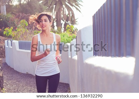 Young woman exercising at an urban path whilst trying to loose some weight