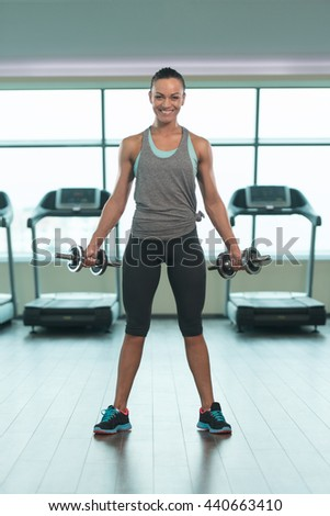Young Woman Exercising Biceps With Dumbbells In The Gym And Flexing Muscles - Muscular Athletic Bodybuilder Fitness Model Doing Dumbbell Concentration Curls - stock photo