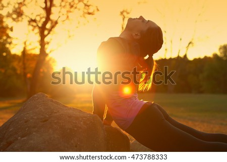 young woman exercising in a park at sunset. A female practicing a yoga pose on a rock with sunlight in front of her.