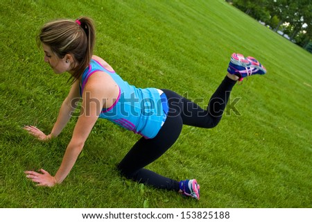Young woman exercising in a park, specifically doing yoga.
