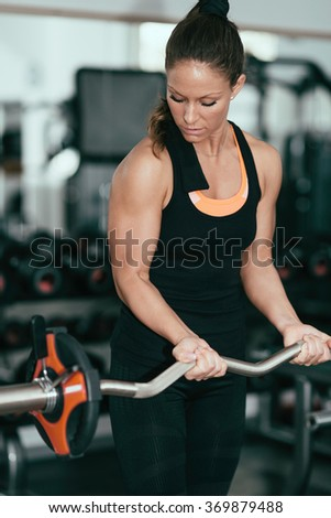 Young woman exercising in gym with barbell weights