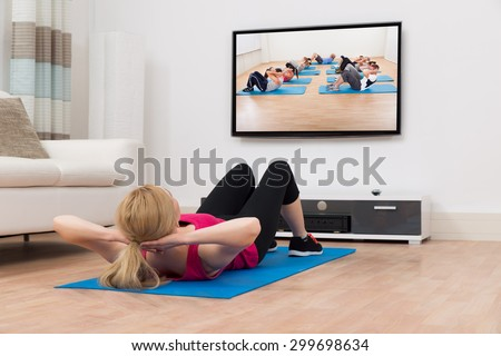 Young Woman Exercising On Blue Mat While Watching Television In House - stock photo