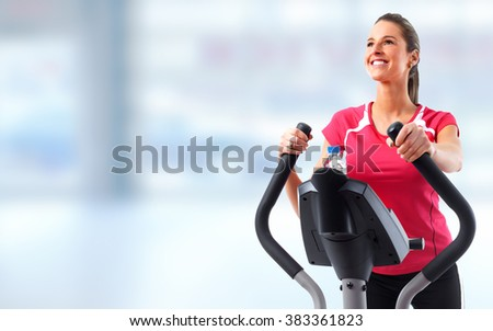 Young woman exercising on elliptical trainer.