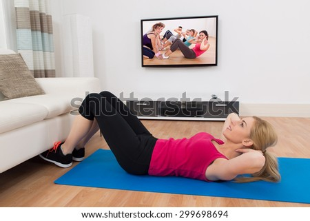 Young Woman Exercising On Exercise Mat In Front Of Television In Living Room - stock photo