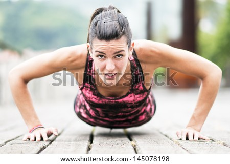 Young Woman Exercising Push-Ups on Wooden Floor. - stock photo