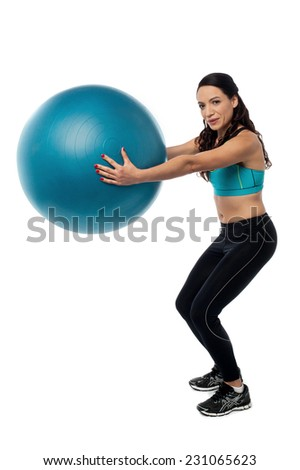 Young woman exercising with a swiss ball
