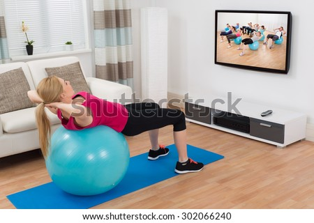 Young Woman Exercising With Blue Fitness Ball While Watching Program On Television