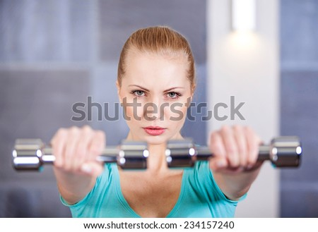 Young woman exercising with dumbbells at the gym training shoulder muscles  - stock photo