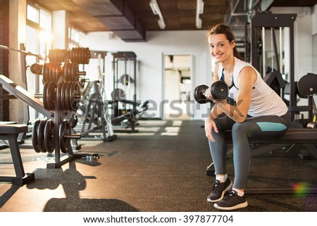 Young woman exercising with dumbbells in gym. - stock photo