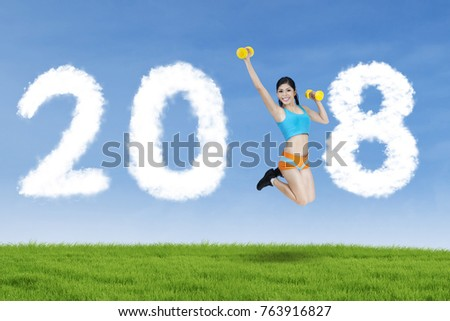 Young woman exercising with two dumbbells in the park while leaping with clouds shaped numbers 2018 in the sky