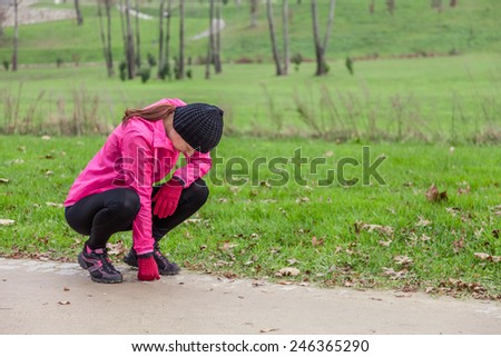 Young woman exhausted after running on a cold winter day in the track of an urban park. - stock photo