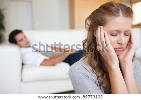 Young woman experiencing headache with man on the sofa behind her - stock photo