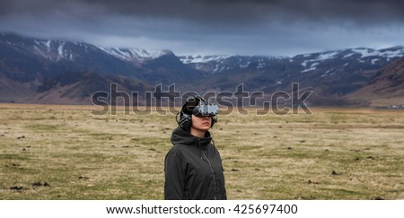 Young woman experiencing virtual reality in the outdoors - stock photo