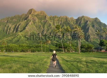 Young woman exploring Kualoa Regional Park under the Hawaiian mountains - stock photo