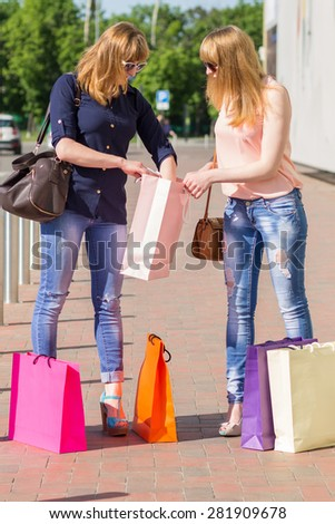 Young woman exploring their shopping bag on the street. Pretty shopping girls with bags near shopping center at summer day - stock photo