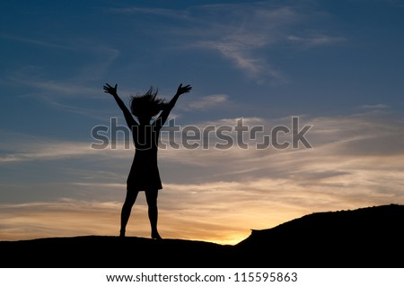 Young woman expresses joy at sunset by flicking her hair. Figure in silhouette