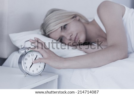 Young woman extending hand to alarm clock in bed at home
