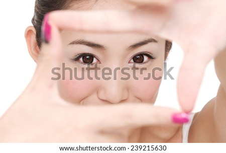 Young woman face and eye care and she making frame with hands, asian beauty - stock photo