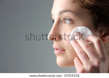 young woman face applying makeup - stock photo