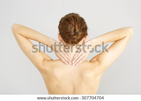 Young woman facing away massaging her neck from an ache or pain - stock photo