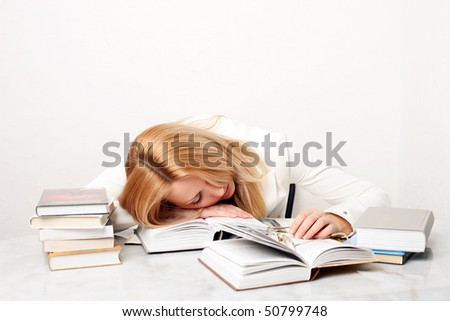 Young woman falling asleep while studying at the table with a lot of books