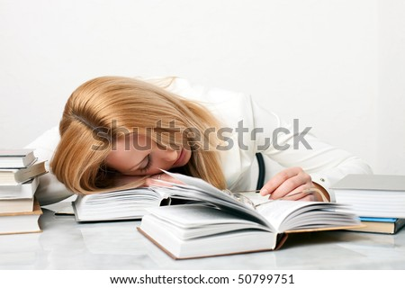 Young woman falling asleep while studying at the table with a lot of books, on white background - stock photo